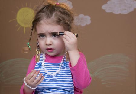 Maquillage pour une petite fille, colorie les lèvres, les cils et les sourcils Banque d'images
