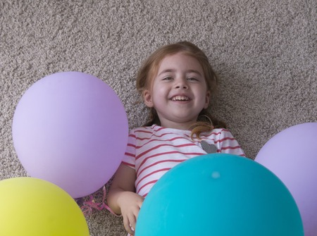 girl with balloons, child with balloons, child with balloons lying on floor. Girl is expressing creativity and looking at the camera and smiling.