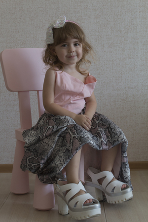 Little funny girl sitting in a chair in her mothers big shoes and dress