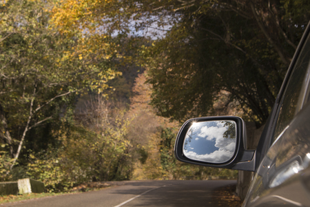Travel concept. Beautiful sky and clouds in sideview car mirror on mountain road Фото со стока