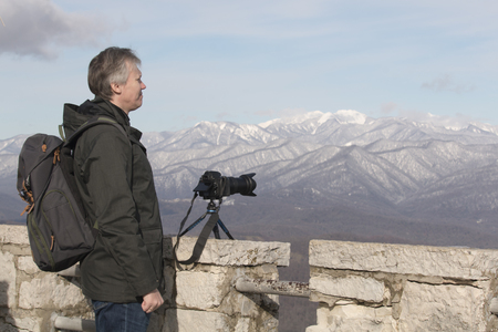 Photographer travels and takes pictures. Location in the mountains. Photographer shooting nature with professional camera