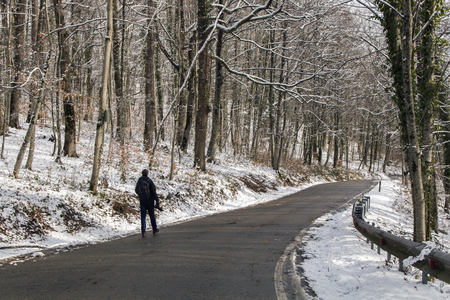 Man with a photo camera walks on the road in the winter forest