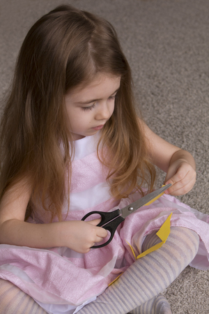 pretty girl scissors paper. cute little girl playing with craft and materials for needlework. Handmade. Stock Photo
