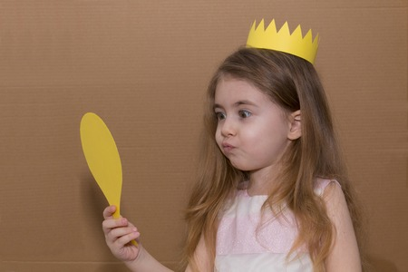 Portrait of emotional little girl with crown a yellow paper holding a mirror. handmade. cardboard background
