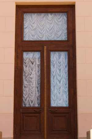 wooden front door with glass and white roman blinds