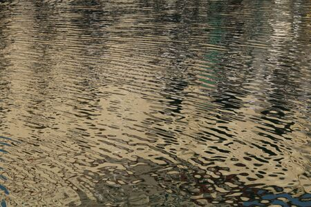 Colorful patterns of blue, brown and white are seen in reflections in the water of a lake.