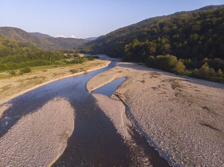 Aerial flight with drone over beautiful green mountains and river.