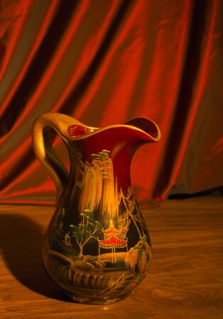 Handmade earthenware jugs painted with ornaments in the countryside stand on a wooden shelf against the red curtain.