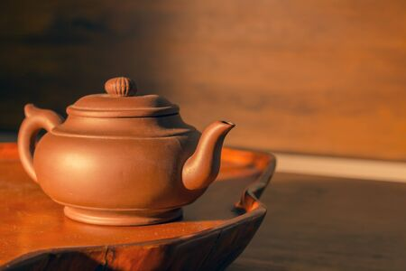 Retro clay Chinese teapot on a brown
