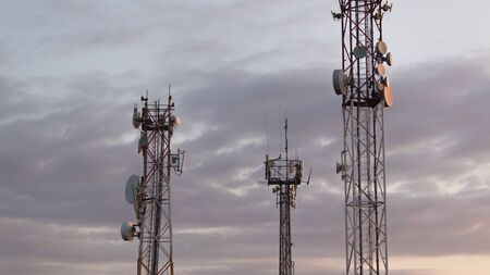 three Communication tower silhouette. Base Station or Base Transceiver Station. Wireless Communication Antenna Transmitter. Telecommunication tower with antennas against sky.