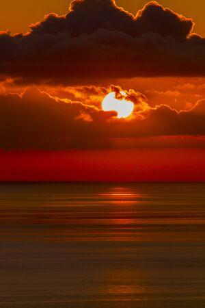 Sunrise on dark sky over sea Фото со стока