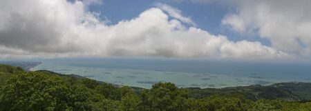 clouds over the sea. green mountains in the foreground. panorama