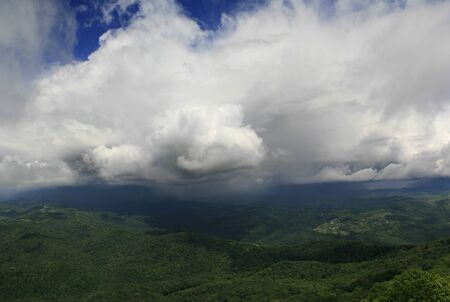 majestic sky with clouds over the green hills. Dramatic clouds over the mountain Фото со стока