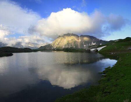 Idyllic summer landscape with clear mountain lake Фото со стока
