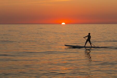 paddle standing board, beach leisure activity, beautiful silhouette of man at sunset. Romantic colorful sunset at the sea. Sun go down Standard-Bild