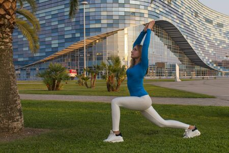 Fitness sport girl in sportswear doing fitness exercise in the street,outdoor sports. Sports girl in light clothing is engaged in gymnastics, fitness woman is stretched Standard-Bild