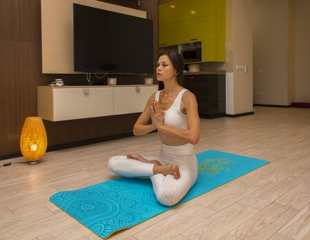 Beautiful girl is doing sports at home practising yoga asanas for health and beauty exercising on floor of apartment. Standard-Bild