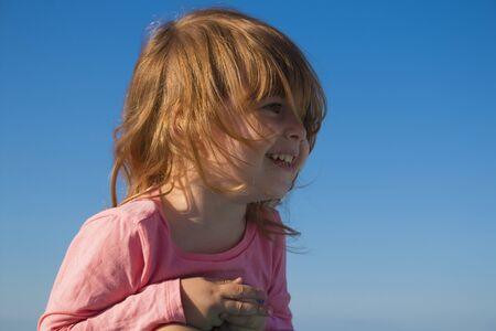 Close-up portrait of a cute, smiling young child on blue sky background