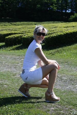 Cute blonde in a white T-shirt and shorts sits on the nature of the summer on a background of green trees Standard-Bild