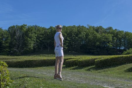 Pretty blonde in a white T-shirt and shorts walks on the nature in the summer against the background of green trees