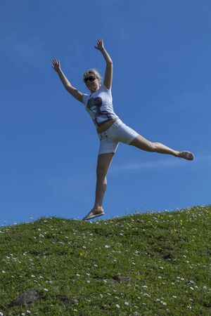 Pretty blonde in sunglasses in a white T-shirt and shorts jumping high in air, against background of summer blue sky.