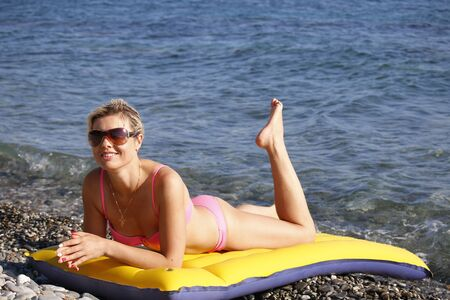 Girl at the sea. Attractive blonde-haired woman sunbathes recline on inflatable swimming mattress on pebble beach Standard-Bild