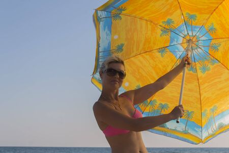 Smiling woman in sunglasses against a blue sky holds a large parasol in his hands