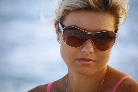 Close-up portrait Beautiful caucasian woman having fun on summer wearing sunglasses on blue sea background. Model looking at camera.