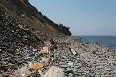 Spilled garbage on the beach. Empty used dirty plastic bottles. Dirty sea sandy shore the Black Sea. Environmental pollution. Ecological problem.