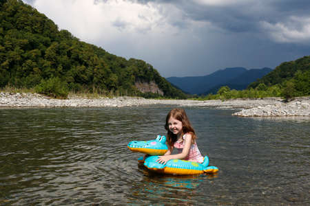 happy laughing girl enjoying swimming in river with rubber ring crocodile. active summer vacation on the beach