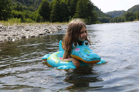 happy laughing girl enjoying swimming in river with rubber ring crocodile