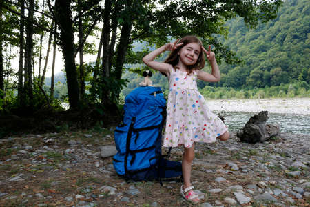 A large backpack for an adult stands next to a little girl against the backdrop of trees and a river, on a sunny day. Standard-Bild