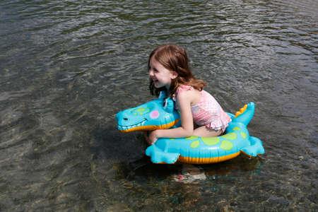 happy laughing girl enjoying swimming in sea with rubber ring crocodile Standard-Bild