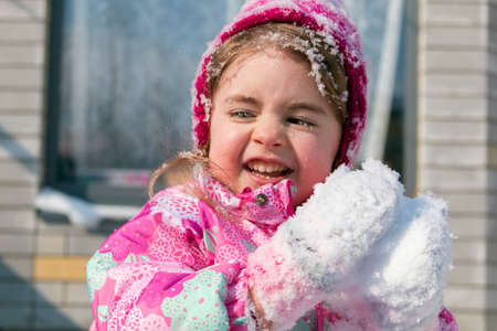 Close up Portrait of cute little girl having fun in the snow