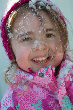 Emotional close up portrait of adorable female child in warm winter clothing, enjoys fresh air and beautiful sunny frosty day, happy to be outdoor