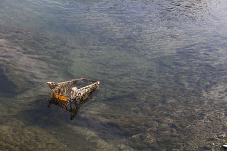A moody shot of a rusty shopping trolley abandoned on a river, symbolizing economic recession and consumer spending crisis