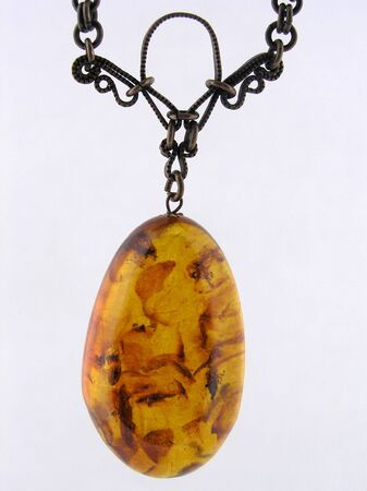 Old vintage amber pendant on white         photo
