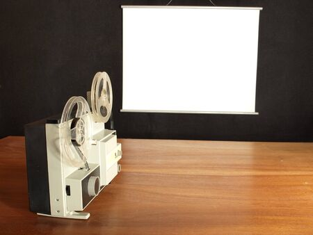 projection screen: Film projector aimed at the screen hangs on a black wall Stock Photo