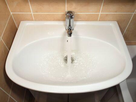 splashback:     White modern ceramic handbasin and chrome tap, water running.