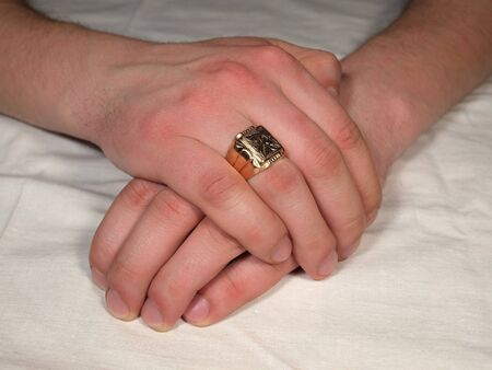 gold table cloth:   Mans hand with a gold ring on his finger against a white tablecloth.