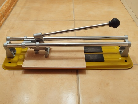 tile cutter: Construction works- ceramic tile cutter with tile.  Stock Photo