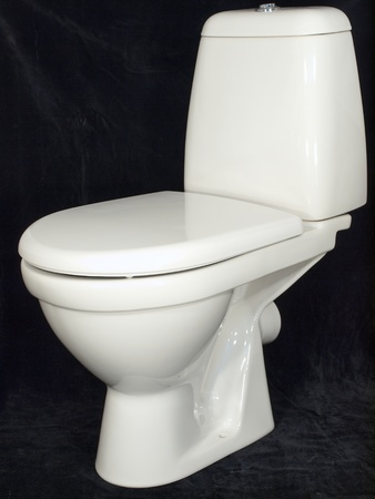White toilet bowl with the lowered cover on a black background        photo