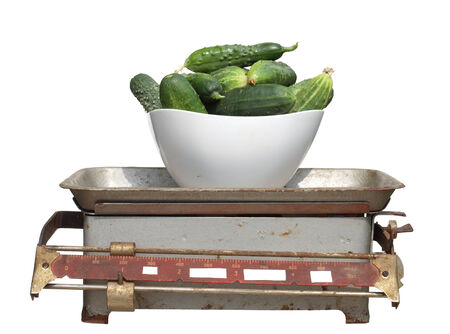 weigher: green cucumbers in a white cup on old mechanical scales isolated on white background.         Stock Photo
