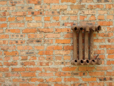 ruined: Ruined cast iron radiator for home on a brick wall.