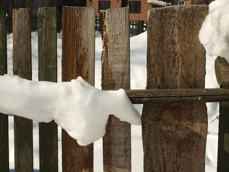 Old wooden village fence covered with snow. Snowy winter in the Moscow region. Russia.