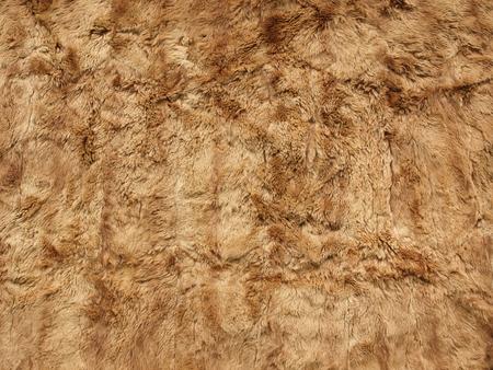 fragment of a fur carpet made of brown sheepskin.