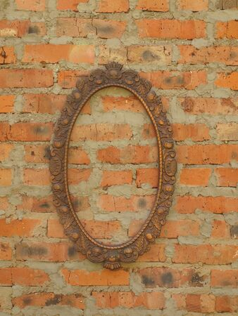 Oval bronze frame on the old brick wall. 版權商用圖片