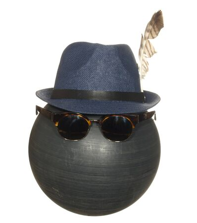 Mens blue hat with a bird feather and dark safety glasses on a black plastic ball isolated on white background.