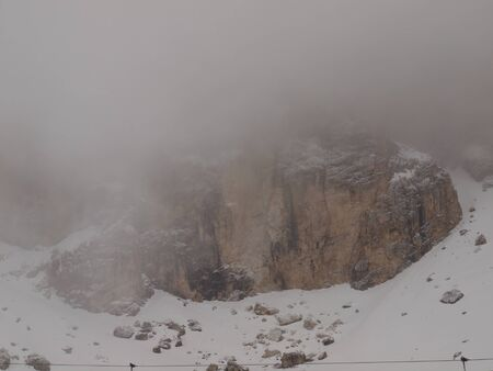 Fog in the mountains. Morning fog covers the rocks in the Italian Dolomites.