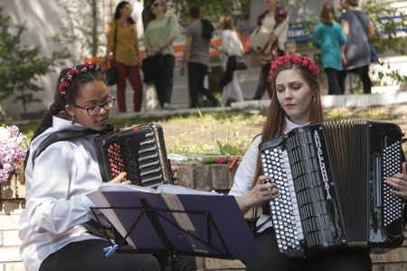 KIEV, UKRAINE - MAY 9, 2016: Girls play the accordion in the Park of Glory during the celebration of Victory Day in Kiev.